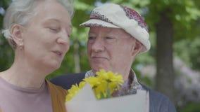Vieux ajouter, femme aux cheveux gris et homme dans l'odeur de chapeau les fleurs et parler jaunes Couples adultes de relations t clips vidéos