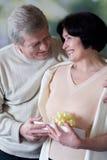 Vieux ajouter heureux au giftbox, souriant et embrassant Photos libres de droits