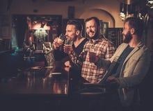 Vieux amis ayant l'amusement et buvant de la bière pression au compteur de barre dans le bar Photos libres de droits