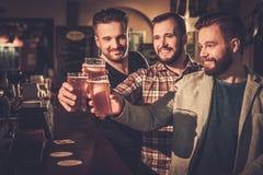 Vieux amis ayant l'amusement et buvant de la bière pression au compteur de barre dans le bar Photographie stock libre de droits