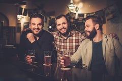 Vieux amis ayant l'amusement et buvant de la bière pression au compteur de barre dans le bar Photo libre de droits