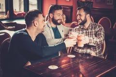Vieux amis ayant l'amusement et buvant de la bière pression dans le bar Image stock