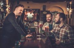 Vieux amis buvant de la bière pression au compteur de barre dans le bar Image stock