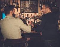 Vieux amis buvant de la bière pression au compteur de barre dans le bar Photo libre de droits