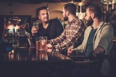 Vieux amis buvant de la bière pression au compteur de barre dans le bar Photographie stock libre de droits