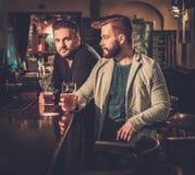 Vieux amis buvant de la bière pression au compteur de barre dans le bar Images libres de droits