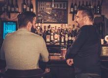 Vieux amis buvant de la bière pression au compteur de barre dans le bar Photos libres de droits