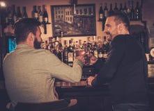 Vieux amis buvant de la bière pression au compteur de barre dans le bar Image libre de droits
