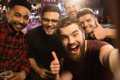 Vieux amis gais ayant l'amusement en prenant le selfie Photographie stock libre de droits