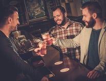Vieux amis gais ayant l'amusement et buvant de la bière pression au compteur de barre Images libres de droits