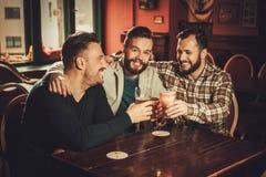 Vieux amis gais ayant l'amusement et buvant de la bière pression dans le bar Photo stock