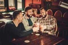 Vieux amis gais ayant l'amusement et buvant de la bière pression dans le bar Photo libre de droits