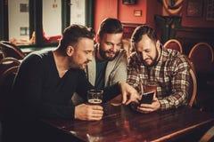 Vieux amis gais ayant l'amusement et buvant de la bière pression dans le bar Image libre de droits