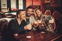Vieux amis gais ayant l'amusement et buvant de la bière pression dans le bar Images libres de droits
