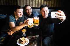 Vieux amis gais ayant l'amusement prenant le selfie et buvant de la bière pression dans le bar Photographie stock
