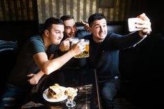 Vieux amis gais ayant l'amusement prenant le selfie et buvant de la bière pression dans le bar Images libres de droits