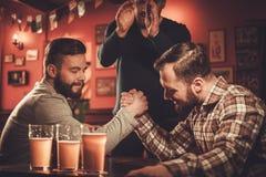 Vieux amis gais ayant le défi de bras de fer dans un bar Photo libre de droits