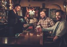 Vieux amis gais buvant de la bière pression au compteur de barre dans le bar Images stock