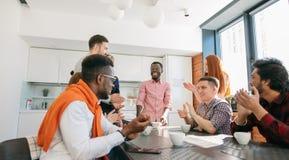 Vieux amis multiraciaux battant des mains et appréciant un diagramme au-dessus de café Images stock