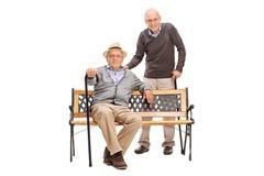 Vieux amis posant ensemble assis sur un banc Images libres de droits