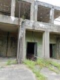 Vieux bâtiment abandonné de ciment avec des mauvaises herbes Photos stock
