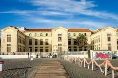 Vieux bâtiment antique avec des fenêtres et des portes et devant un palmier s'élevant sur le bord de mer près du port de Rome Images stock
