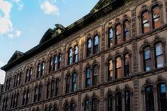 Vieux bâtiment, avec des fenêtres réfléchissant la lumière Photos libres de droits