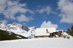 Vieux bâtiment en pierre dans les Alpes français avec les montagnes couvertes par neige dominant derrière images libres de droits