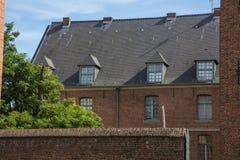 Vieux bâtiment européen brun avec des murs de briques, des arbres verts et le ciel bleu Photos stock