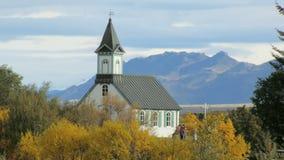 Vieux bâtiment islandais traditionnel en parc dans le jour d'automne à l'arrière-plan de la montagne clips vidéos