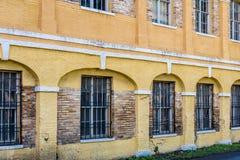 Vieux bâtiment jaune avec des barres sur les fenêtres Images libres de droits