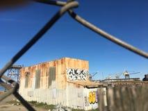 Vieux bâtiment ondulé et d'abandon avec le graffiti derrière la clôture Photos libres de droits