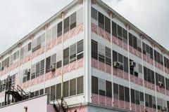 Vieux bâtiment rose et blanc avec des climatiseurs de fenêtre Images libres de droits