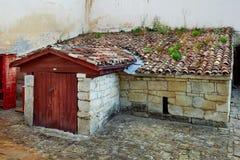 Vieux bâtiment rustique de pierre avec un toit carrelé avec de la mousse photographie stock