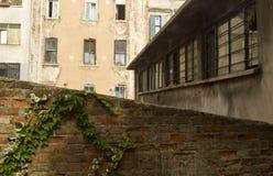 Vieux bâtiments avec les fenêtres étroites et vieux mur de briques Photographie stock libre de droits