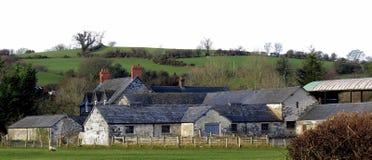 Vieux bâtiments de ferme contre le flanc de coteau vert Photos libres de droits