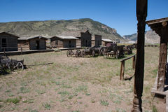 Vieux bâtiments de rondin occidentaux abandonnés et chariots en bois Image libre de droits