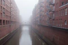Vieux bâtiments industriels dans le port brumeux de la ville allemande Image stock