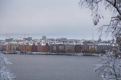 Vieux bâtiments par la rivière un jour humide d'hiver avec la neige et la brume, Stockholm Suède photographie stock