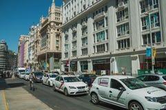 Vieux bâtiments sur la rue passante avec le cycliste et les voitures à Madrid photo libre de droits