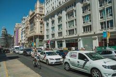 Vieux bâtiments sur la rue passante avec le cycliste et les voitures à Madrid photographie stock