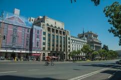 Vieux bâtiments sur la rue passante avec le cycliste et les voitures à Madrid image stock