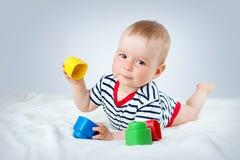 Vieux bébé de neuf mois se situant dans le lit sur la couverture blanche Images stock