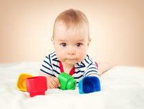 Vieux bébé de neuf mois se situant dans le lit sur la couverture blanche Photographie stock