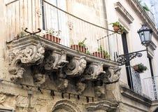 Vieux balcon baroque de émiettage avec des planteurs, Lecce Italie Photographie stock libre de droits