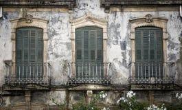 Vieux balcons rouillés avec les portes fermées vertes Photographie stock libre de droits