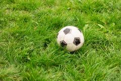 Vieux ballon de football épluché sale sur l'herbe photo libre de droits