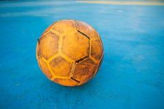 Vieux ballon de football jaune sur le terrain de football bleu photos stock