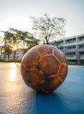 Vieux ballon de football jaune sur le terrain de football bleu image stock