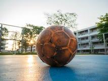 Vieux ballon de football jaune sur le terrain de football bleu photo libre de droits